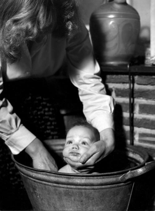 8711-1 Moeder stopt kind in bad
